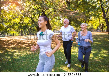 Senior man and woman and young female instructor  workout on fresh air. Outdoor activities, healthy lifestyle, strong bodies, fit figures. Stylish, modern sportswear. Different generations #1215526588