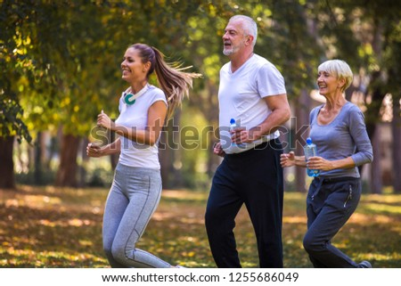 Senior man and woman and young female instructor  workout on fresh air. Outdoor activities, healthy lifestyle, strong bodies, fit figures. Stylish, modern sportswear. Different generations #1255686049