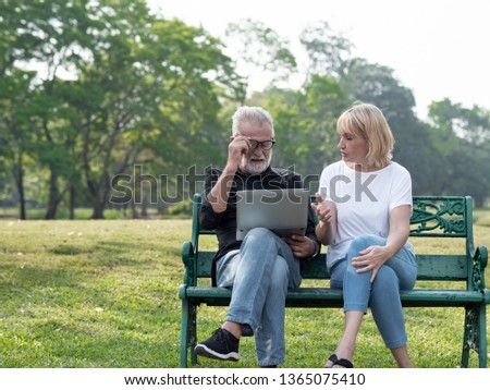 Senior man and woman couple connected on laptop computer in a park on a sunny day. relax in the forest spring summer time. free time, lifestyle retirement grandparents concept.