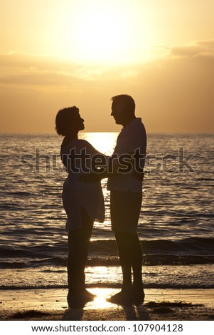 Senior man and woman couple embracing together at sunset on a beautiful tropical beach