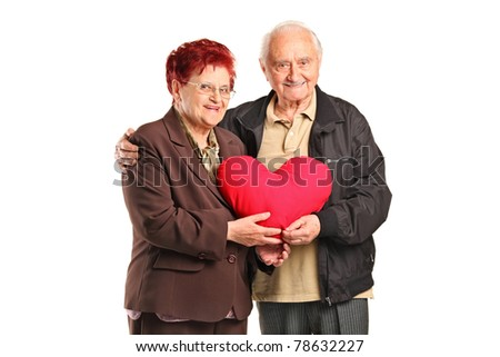 Senior man and woman holding a heart shaped pillow isolated on white background