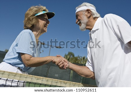 Senior man and woman shaking hands after playing tennis