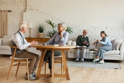 Senior man and woman sitting at table and enjoying talk, another aged couple interacting in background sitting on sofa in common room of nursing home