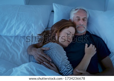 Senior man and woman sleeping and dreaming together in a deep sleep. Mature woman embracing and sleeps on her husband's chest while sleeping at night. Loving couple resting in their bed, copy space. Stock fotó ©