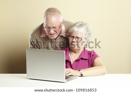 Senior man and woman using laptop whilst looking confused