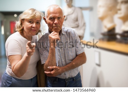 Senior man and woman visiting exposition of museum with exhibits of art