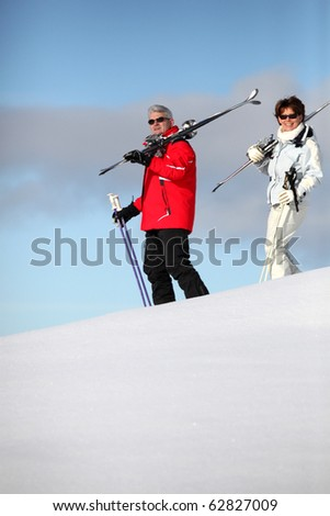 Senior man and woman with skis in the snow