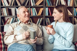 Senior man and young woman at home library sitting on sofa drinking hot tea smiling joyful talking about life