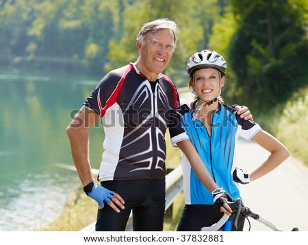 Senior man and young woman on road bike. Copy space