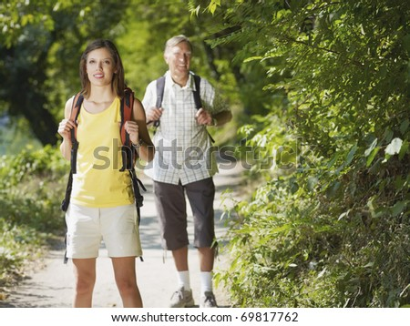 senior man and young woman walking with backpack in wood, looking at camera and smiling. Horizontal shape, front view, copy space