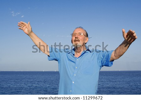 senior man arms open to the skies - stock photo