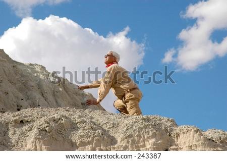 Senior man ascending a high mountain. To see all four images in this series keyword: khaki/man