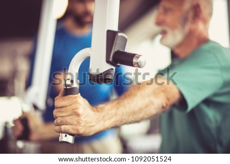 Senior man at gym working exercise for hands and talking with trainer. Close up. Focus is on hand.