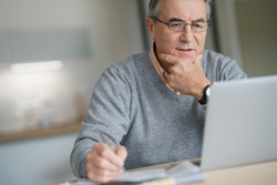 Senior man at home connected on laptop computer