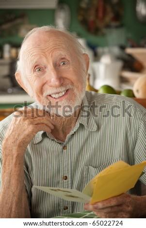 Senior man at home reading greeting card