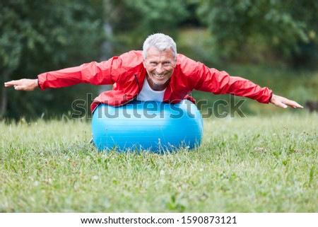 Senior man balances during a back exercise on an exercise ball in the park
