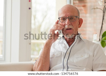 Senior man calling with portable phone in living room.