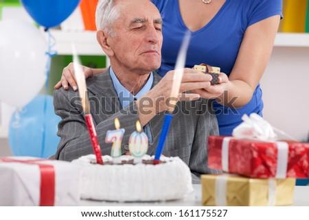 senior man celebrating 70th birthday and receiving birthday gift