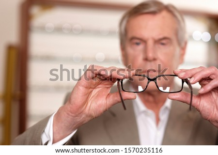 Senior man choosing eyeglasses in optician's office