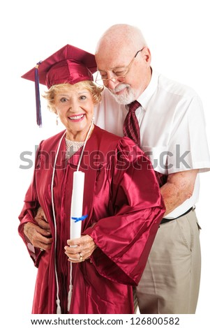 Senior man congratulates his successful wife on her college graduation.  Isolated on white.