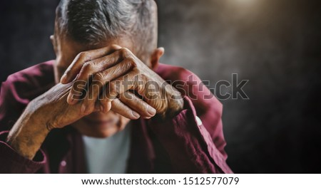 senior man covering his face with his hands. Depression and anxiety Copy space. in dark background Stock photo ©