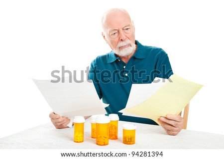 Senior man depressed by a pile of medical bills.  Isolated on white.