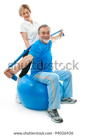 Senior man doing fitness exercise with help of trainer at sport gym