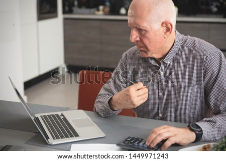 Senior man doing some paperwork and calculations at home. Pensioner counts money, tax calculation concept