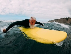 Senior man doing surf with longboard riding a wave - Mature person having fun doing extreme sport - Joyful elderly concept - Focus on his face