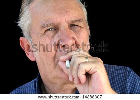 Senior man dragging on a cigarette staring down the barrel.