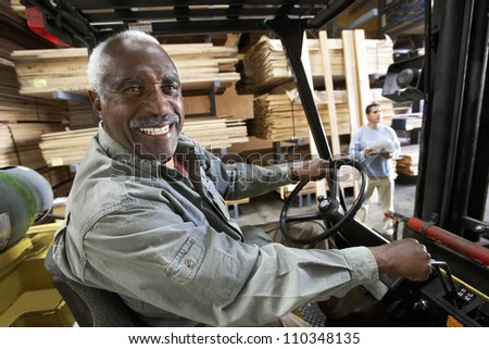 Senior man driving forklift