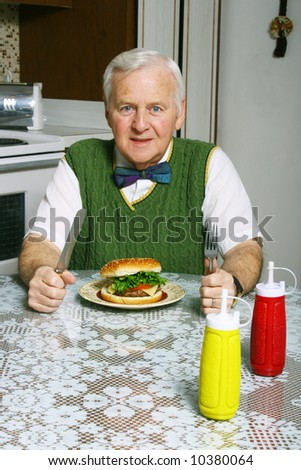 Senior man eating a burger