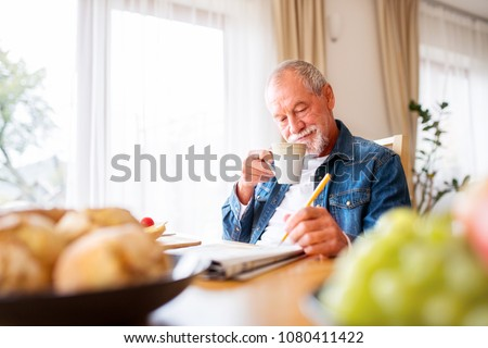 Senior man eating breakfast and doing crosswords at home. Foto stock ©