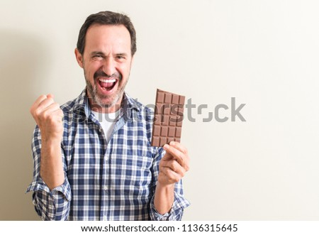 Senior man eating chocolate bar screaming proud and celebrating victory and success very excited, cheering emotion
