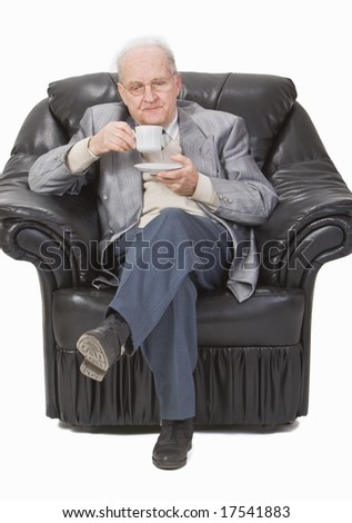 Senior man enjoying a cup of tea in his office armchair.