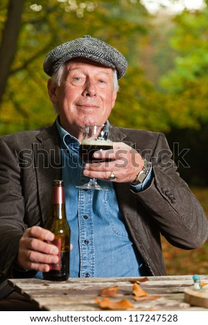 Senior man enjoying dark beer and cheese outdoors in autumn forest.