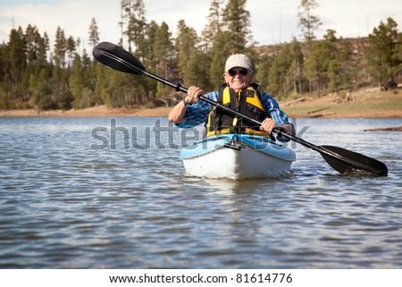 Senior Man Enjoying Kayaking on Lake - stock photo