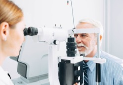 Senior man examined by an ophthalmologist, eye exam