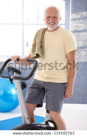 Senior man exercising on fitness cycle, smiling.