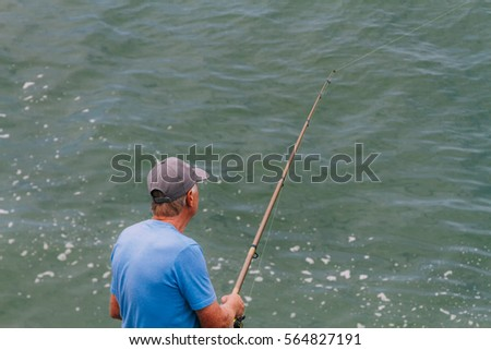 Senior man fishing alone in the sea seen from above #564827191