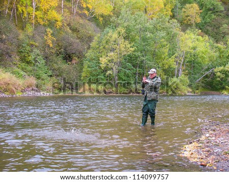 Senior man fishing in Raduga river (Kamchatka, Russia)