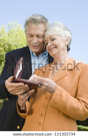 Senior man gifting necklace to his wife - stock photo