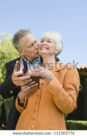 Senior man gifting necklace to woman