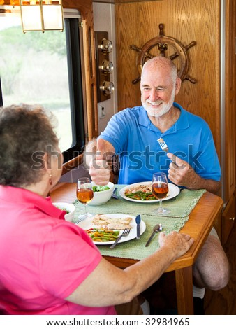 Senior man gives his wife a big thumbs up for the delicious dinner she made in their motor home.