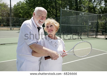 Senior man gives his wife pointers on tennis.