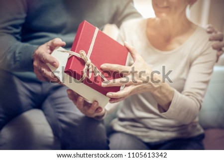 Senior man giving present to his wife. Close up. Focus is on box.