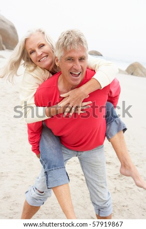 Senior Man Giving Woman Piggyback On Winter Beach