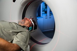 Senior man going through a Computerised Axial Tomography (CAT) Scan medical test, examination in a modern hospital (colour toned image; shallow DOF)