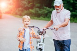 Senior man grandfather and grandson talking while walking with bicycle in the park. Family, generation, safety and people concept. Sun glare effect.