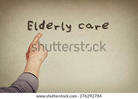 senior man hand pointing at text with the phrase elderly care. room for text